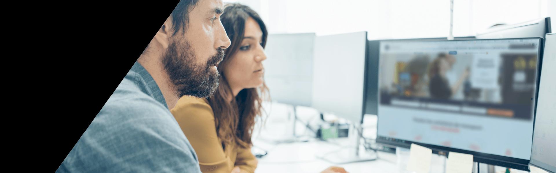 2 personnes regardant un ordinateur avec le site d'Arvey affiché