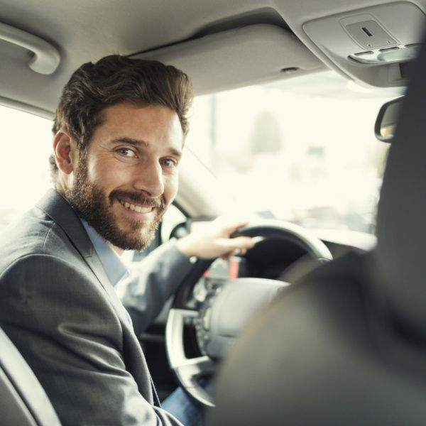 Chauffeur souriant au passager arrière